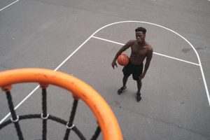 man waiting for new jersey to come out under basketball hoop